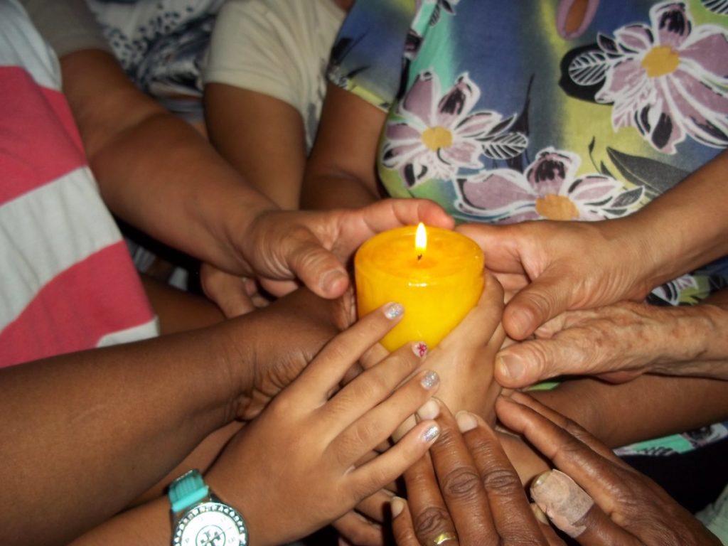 mains autour de la bougie, signifiant la prière autour du Christ notre centre